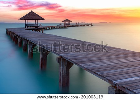 Wooded bridge in the port between sunrise. - stock photo