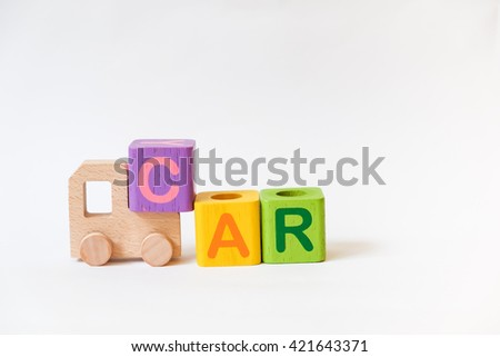 Wooden ABC Blocks and Wooden Car Toy on gray background with copyspace - stock photo
