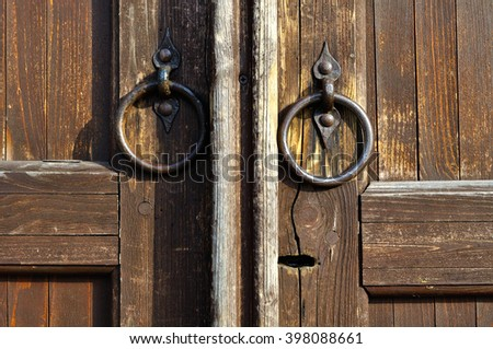 Wooden aged door with keyhole and shabby metal door handles in the form of ring. Architectural vintage background. Retro tones processing  - stock photo