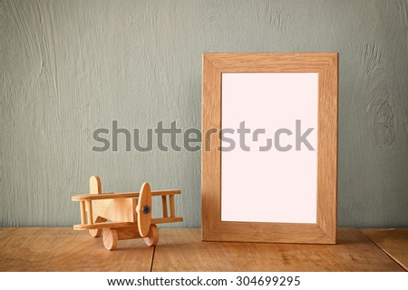 wooden airplane toy over wood table next to blank photo frame. retro filtered image  - stock photo