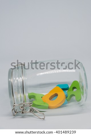 Wooden alphabet IDEA word in the glass bottle with white background in Vertical view and selective focus - stock photo