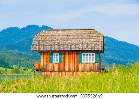 Wooden alpine house shore of Weissensee lake in summer landscape of Alps Mountains, Austria - stock photo