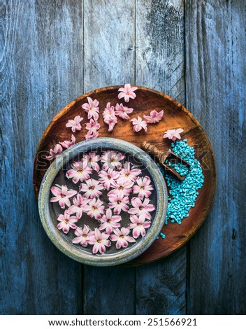Wooden and blue bowl with pink flowers and water,  scoop with sea salt on old background , top view - stock photo