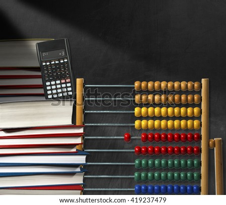 Wooden and colorful abacus, a stack of books and a modern calculator on a empty blackboard with copy space - stock photo
