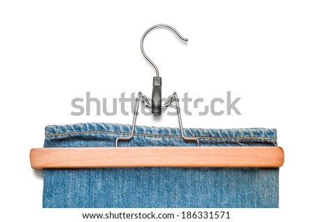 Wooden and metallic trousers hanger with blue jeans, isolated on white background - stock photo