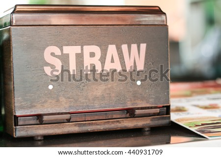 Wooden and Plastic Drinking Straw Box, Food Menu Beside, on Reception Counter Table at Cafe or Fast Food Restaurant. Very Shallow Focus.
