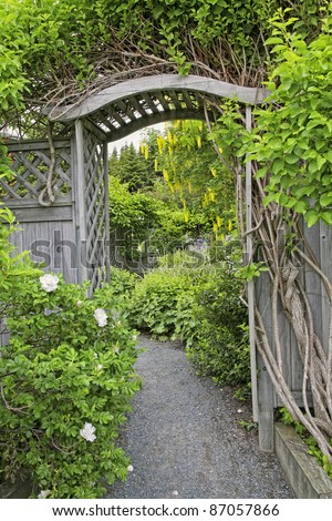 Wooden arbor and fence in a perennial garden or park like setting. - stock photo