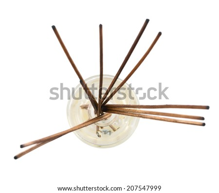 Wooden aroma sticks in a glass flask filled with flavor liquid substance isolated over white background, top view - stock photo