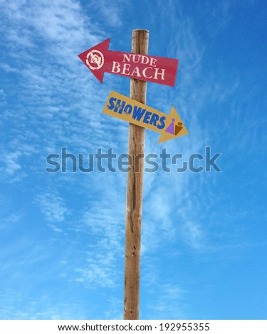 wooden arrow direction signs post to the nude beach and showers against a blue sky - stock photo