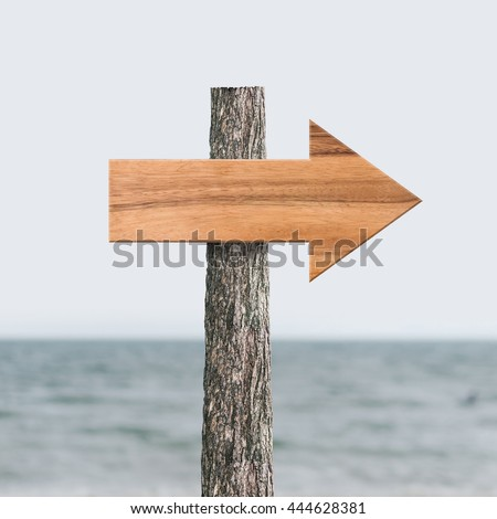Wooden arrow sign board texture background in beach and sea area.