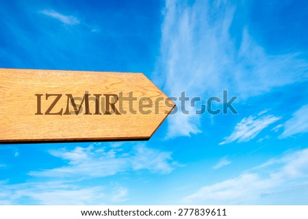 Wooden arrow sign pointing destination IZMIR, TURKEY against clear blue sky with copy space available. Travel destination conceptual image - stock photo