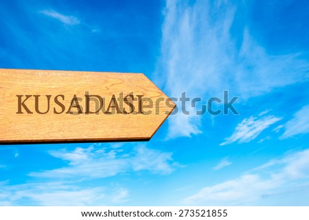 Wooden arrow sign pointing destination KUSADASI, TURKEY against clear blue sky with copy space available. Travel destination conceptual image - stock photo