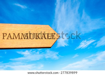 Wooden arrow sign pointing destination PAMMUKALE, TURKEY against clear blue sky with copy space available. Travel destination conceptual image - stock photo
