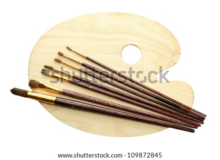 wooden art palette and brushes isolated on white - stock photo