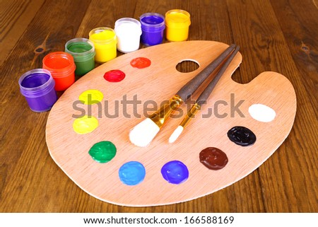 Wooden art palette with paint and brushes on table close-up