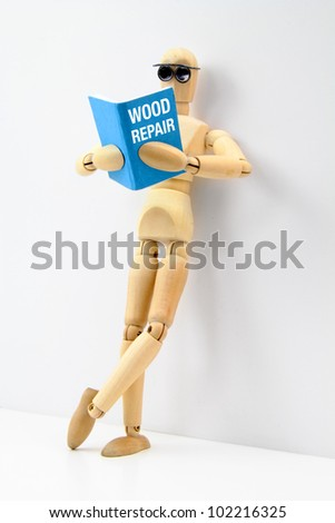 Wooden artist manikin reading a book on wood repair while leaning on a wall. - stock photo