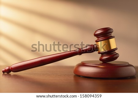 Wooden auctioneer or judges gavel for dispensing justice or knocking down sale prices against a background with rays of sunlight and shadow - stock photo