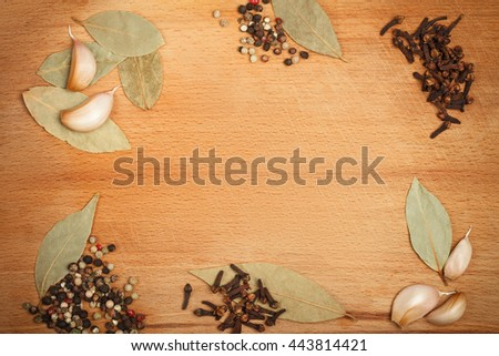 Wooden background framed with different spices with empty space in central part - stock photo