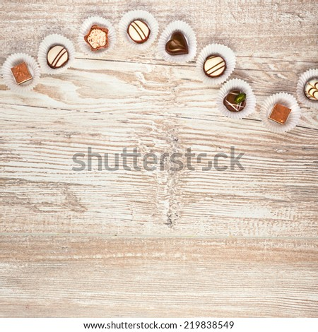 Wooden background with a row of chocolate pralines, square framing, text space - stock photo