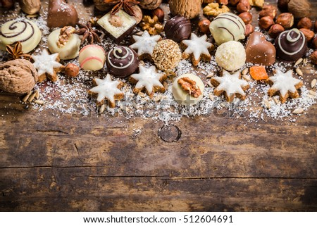 wooden background with candies, nuts, cookies, chocolate, dried fruits and other sweets, empty space for text