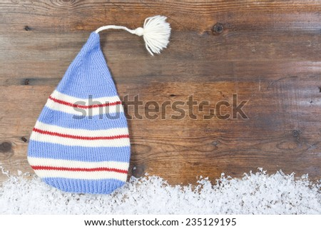 Wooden background with cap, snow on the border and copyspace for your Christmas text - stock photo