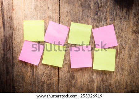 Wooden background with eight blank colorful sticky notes - stock photo