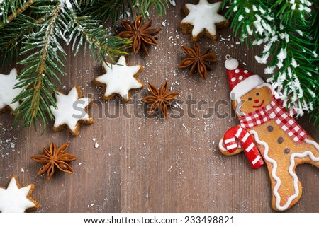 wooden background with fir branches, cookies and gingerbread man, top view - stock photo