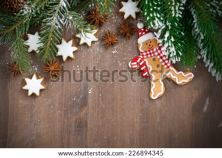 wooden background with fir branches, cookies and gingerbread man, top view, close-up - stock photo