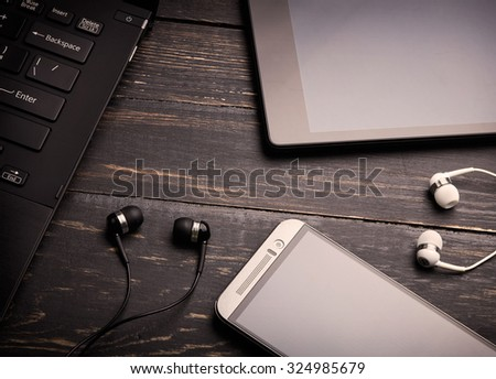 Wooden background with gadgets. Sepia toned - stock photo
