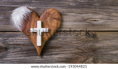 Wooden background with olive heart and white cross for an obituary notice. - stock photo