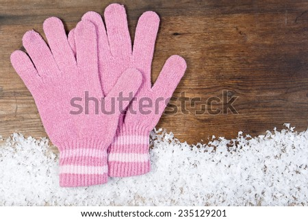 Wooden background with pink mittens winter snow on the border and copyspace for your Christmas text - stock photo