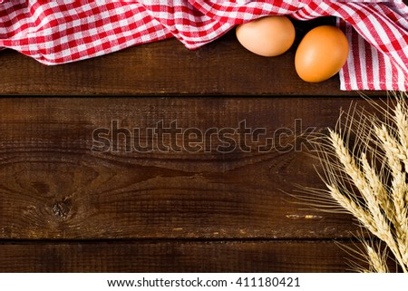 Wooden background with plaid kitchen towel, fresh chicken eggs and golden wheat ears. Copy space for text - stock photo