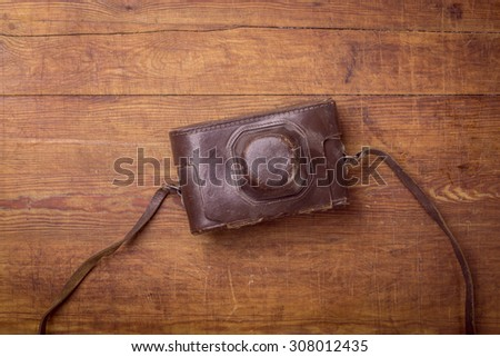 wooden background with retro still camera in case - stock photo