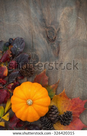 wooden background with seasonal pumpkin and leaves, vertical closeup, top view - stock photo