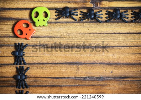 Wooden background with spiders and skulls - stock photo