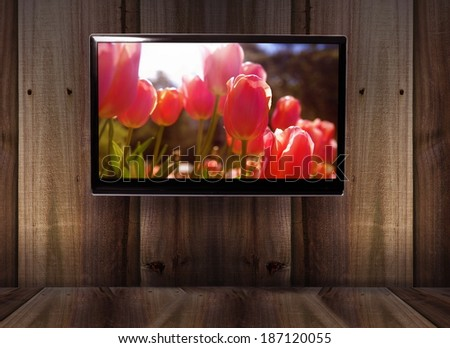 wooden background with tv and tulips picture