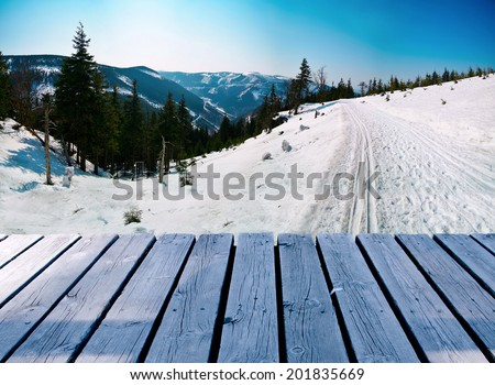Wooden balcony on winter landscape with skiing path - stock photo