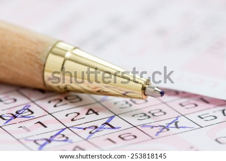 Wooden ballpen and lotto ticket with chosen numbers - stock photo
