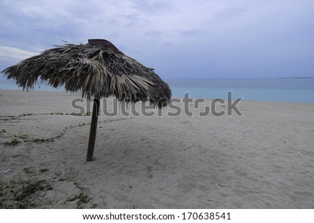 Wooden bamboo umbrella on a tropical sugar-white Varadero beach in Cuba. Varadero is one of the top destination in Cuba to enjoy an all inclusive vacation. - stock photo