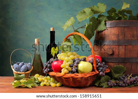 Wooden barrel and fresh fruit in a wicker basket - stock photo