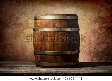 Wooden barrel on a table and textured background - stock photo