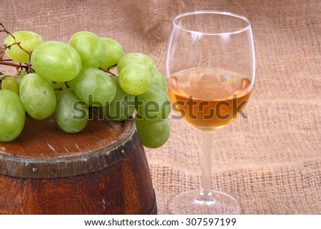 wooden barrel with glass of wine and grapes - stock photo