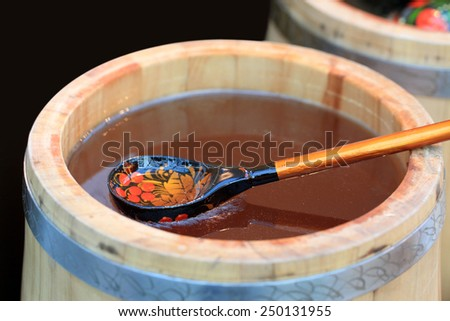 Wooden Barrel with honey and a wooden spoon - stock photo