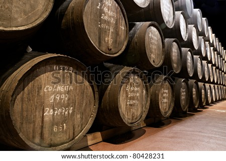wooden barrels hold Port fortified wine to mature in wine cellars in Villa Nova de Gaia, Portugal - stock photo
