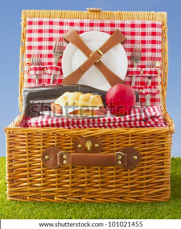 Wooden basket for picnic with sandwich, wine and apple over a grass field - stock photo