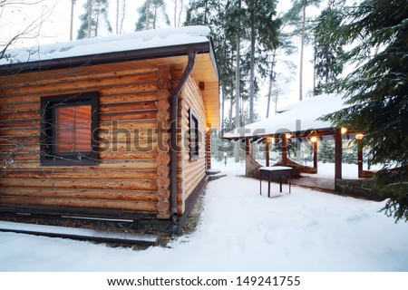 Wooden bath, barbecue for meat and canopy among pines and firs at winter evening. - stock photo