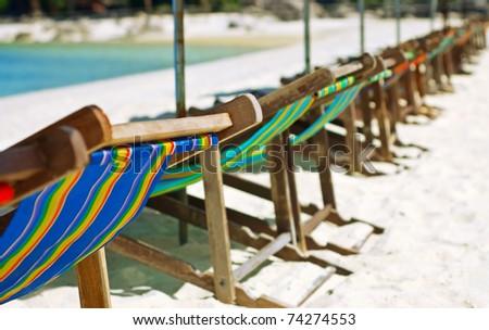 Wooden beach chairs under umbrella. - stock photo