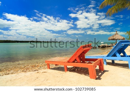 Wooden beach lounge chairs along the shoreline of the Florida Keys with pretty blue sky and clouds and thatched hut in the background. - stock photo