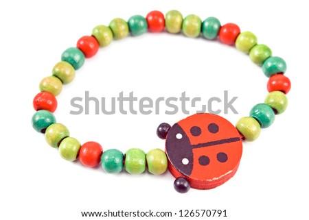 Wooden beads bracelet with ladybug isolated on white - stock photo