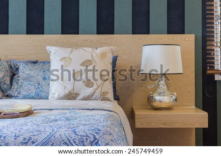 wooden bed with pillows and lamp in bedroom at home - stock photo